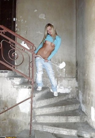 Young slut undressed in the entrance and posing for the camera
